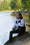 Man in historical costume. Sitting near the lake Royalty Free Stock Photography