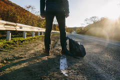 Man hitchhiking on a country road. Traveler showing thumb up on for hitchhiking during road trip. Adventure and tourism concept Royalty Free Stock Image