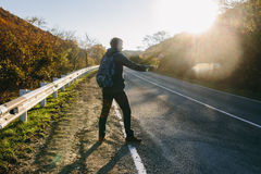 Man hitchhiking on a country road. Traveler showing thumb up on for hitchhiking during road trip. Adventure and tourism concept Stock Image