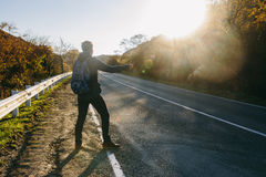 Man hitchhiking on a country road. Traveler showing thumb up on for hitchhiking during road trip. Adventure and tourism concept Stock Photos