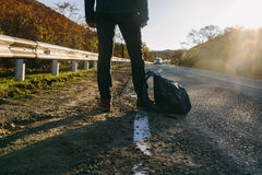 Man hitchhiking on a country road. Traveler showing thumb up on for hitchhiking during road trip. Adventure and tourism concept Royalty Free Stock Photo