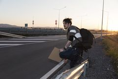 Man hitchhiking on a road. Selective focus. Sunset time. Back light Stock Images