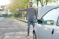 Man and car engine breakdown problem. Man hitchhiking on the road after a vehicle breakdown Royalty Free Stock Photos