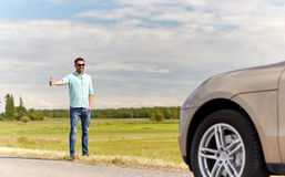 Man hitchhiking and stopping car at countryside. Road trip, hitchhike, travel, gesture and people concept - man hitchhiking and stopping car with thumbs up Royalty Free Stock Photo