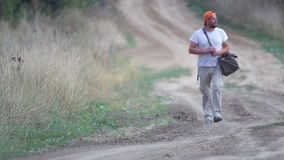 A man hitchhiking on a village road. A young bearded man stops a car in a field. stock footage