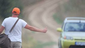 A man hitchhiking on a village road. A young bearded man stops a car in a field. stock video