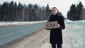 Man hitchhiking at winter country road with cardboard plate stock video
