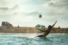 Man hits ball while in the water on beach Royalty Free Stock Photo