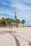 Man Hits Jump Serve In Pickup Miami Beach Volleyball Game. Miami, FL, USA - December 27, 2014:  A man hits a powerful jump serve in a pickup game of beach Royalty Free Stock Image