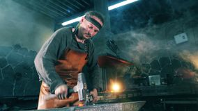 Man hits a metal knife with a hammer while working at a forge. 4K stock video