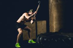 Man Hits Tire - Workout At Gym With Hammer And Tractor Tire Siluet. Athletic Man Hits Tire - Workout At Gym With Hammer And Tractor Tire Siluet Stock Photography
