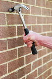Man hitting a brick wall with a hammer Stock Image