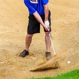 Man hitting golf ball out of a bunker stock images