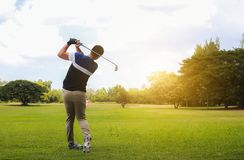 Man hitting golf shot with club on course while summer in the sun. Man hitting golf shot with club on course while summer in the sun royalty free stock image