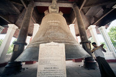 Man hitting the Mingun bell in Myanmar. Royalty Free Stock Images