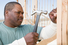 A man hitting a nail with a hammer Stock Images