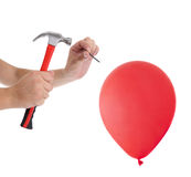 Man hitting a nail into a red balloon Royalty Free Stock Photography