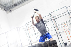 Man hitting tire with sledgehammer in crossfit gym Stock Photos
