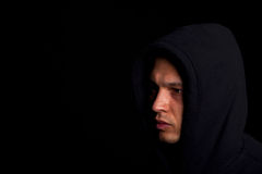 Man with hoddie. Stylish young man with hoddie over a black background Stock Photography