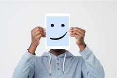 Man hoding tablet frame in hand isolated on white closeup. Happy smile on it. Positive human emotion. African man hoding tablet frame in hand isolated on white stock photo