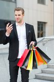 Man hold bags while check discount online with smartphone. Guy carry bunch shopping bags. Profitable deals shopping on. Black friday. Man hold paper bags after stock image