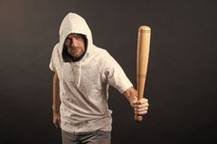 Man hold baseball bat, agression. Hooligan wear hood in hoody, fashion. Gangster guy threaten with bat weapon royalty free stock image