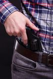 Black weapon in the man`s hand. The man hold the black revolver behing his girdle. He holds one of his fingers on the raised cock royalty free stock photos