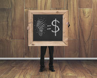 Man hold blackboard with hand-drawn ideas equal money concept. On teak wooden wall and floor background stock photo