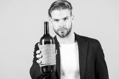 Man hold bottle of wine, alcohol. Macho with bottle, bad habits. Sommelier or degustator with wine, winery. Alcohol royalty free stock image