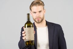 Man hold bottle of wine, alcohol. Macho with bottle, bad habits. Sommelier or degustator with wine, winery. Alcohol addiction, bad. Man hold bottle of wine Royalty Free Stock Images