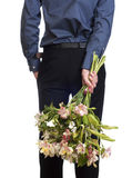Man hold bouquet of flowers behind his back. Stock Image