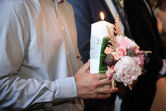 Man hold a candle and wedding bouquet in church Royalty Free Stock Image