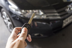 Man hold car remote key for unlock or lock the black car in back. Ground stock image