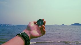 Man hold compass with sea and mountain at the background. stock photos