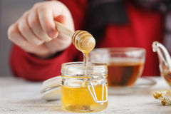 Man hold cup of hot tea in glass cup, jar of honey, honey dipper Stock Photography