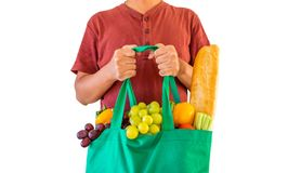 Man hold reen reusable shopping bag filled with full fresh fruits and vegetables grocery product. Man hold eco friendly green reusable shopping bag filled with royalty free stock image