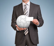Man hold empty card and jigsaw puzzle sphere Stock Image