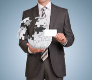 Man hold empty card and jigsaw puzzle sphere Royalty Free Stock Image