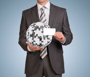 Man hold empty card and jigsaw puzzle sphere Royalty Free Stock Photos