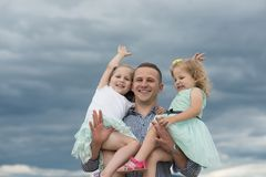 Man hold girls on cloudy grey sky. Father and daughters happy smile on summer day outdoors. Fathers day concept stock image