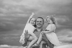 Man hold girls on cloudy grey sky. Father and daughters happy smile on summer day outdoors. Fathers day concept Stock Photo