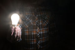 Man hold glow lamp in hand Stock Photo