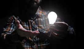 Man hold glow lamp in hand Royalty Free Stock Photo