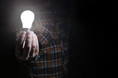 Man hold glow lamp in hand Stock Image