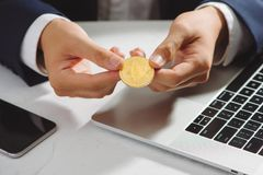 Man hold gold bitcoin over office desk. Bitcoin payment concept. royalty free stock image