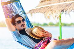 A man hold hat and sleep on hammock near the river. royalty free stock photography