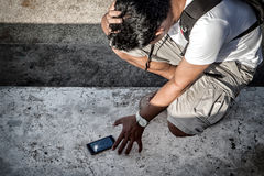 Man hold the head with hand and grab a broken smartphone with cr. Ashed screen on the concrete floor stock photo