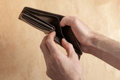 Man hold in his arm empty purse stock images