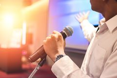 The man hold microphone on the stage. The man hold microphone near the stage royalty free stock photography