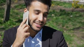 Caring son speaks with mom on phone and smiles with dimples.r. Man hold phone in hand and talking with mom. Son has dimple on cheeks, beard, short hair and long stock photography